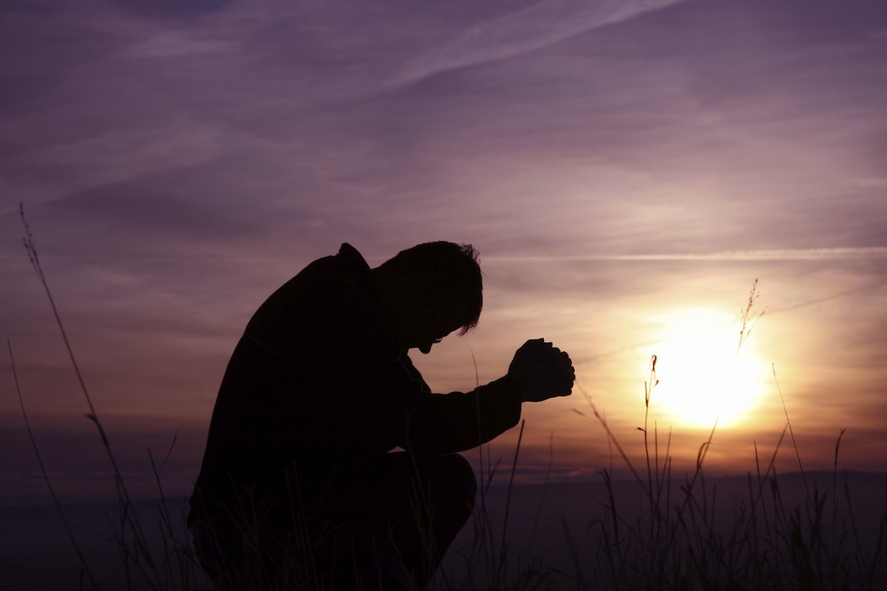 man-praying-silhouette-purple-sunset.jpg