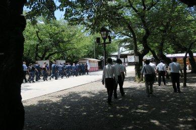 戦闘服の人たちと白シャツの一団