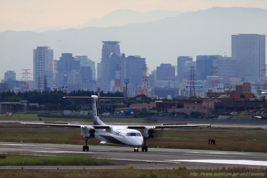 大阪キタの街並みwith ANA WINGS DHC-8-402Q / JA???A@RWY14Lエンド・エアフロントオアシス下河原