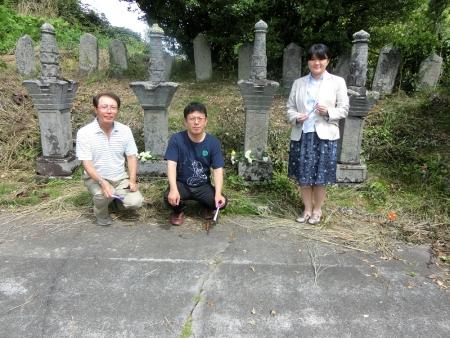 手塚光盛の墓の前で