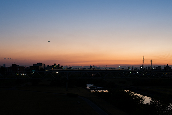 夕焼けの矢田川と飛行機