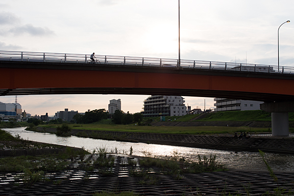 橋を渡る自転車と河原のおじさん