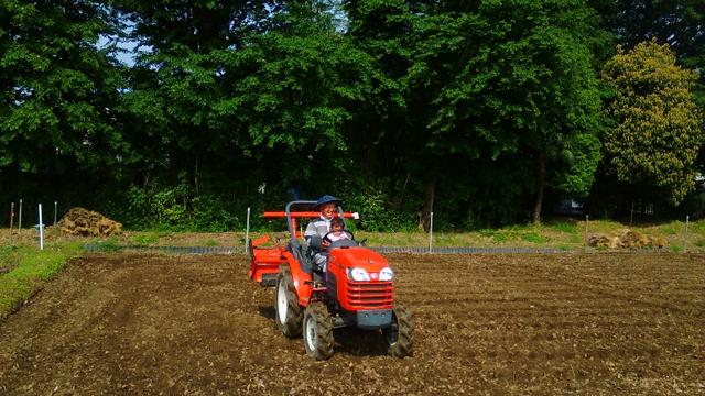 田んぼで初めてトラクターに乗る子供