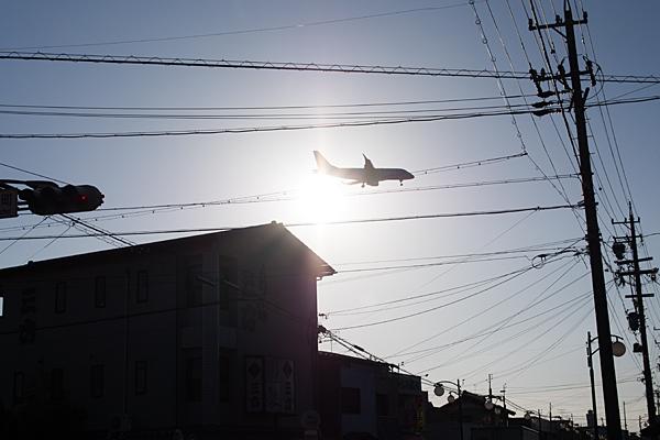 街中上空を低空で飛ぶ飛行機