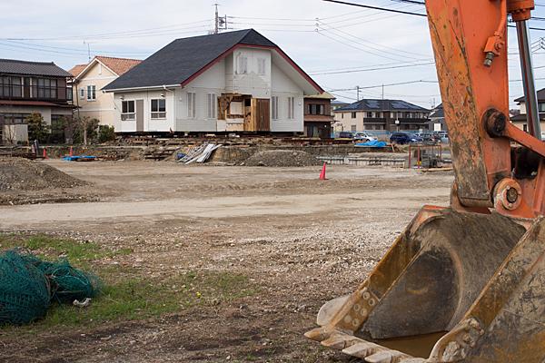 ショベルカーと解体中の家