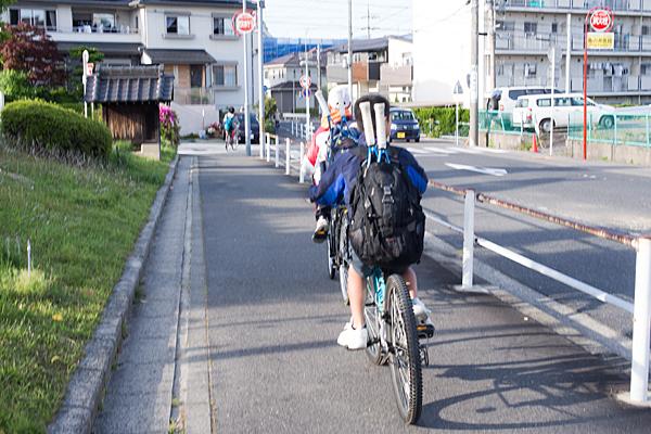 テニスラケットを背負った自転車小学生