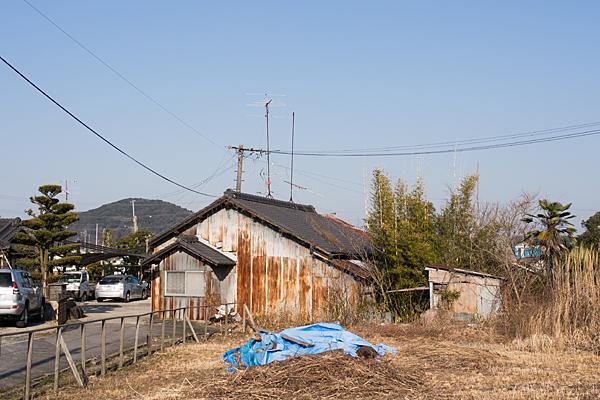 古びた家屋と冬枯れの空き地