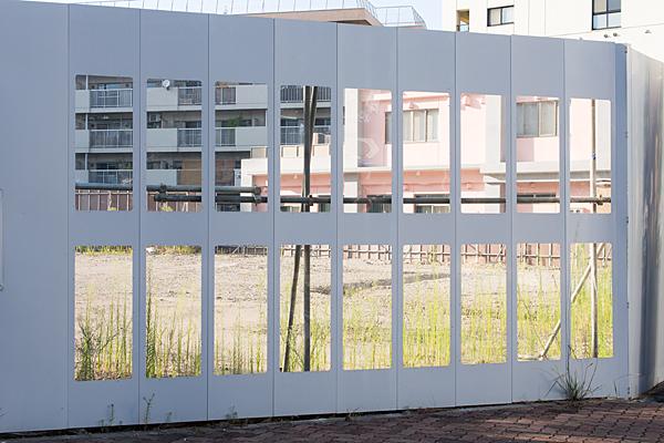 空き地とフェンスと夏の雑草