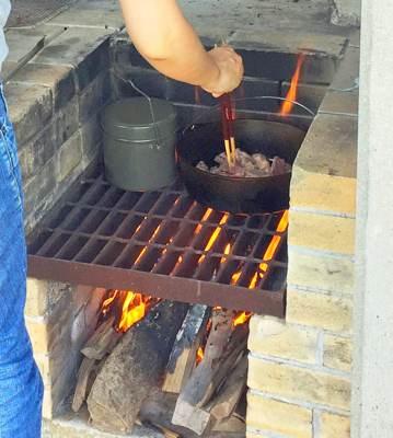 薪の火で調理中